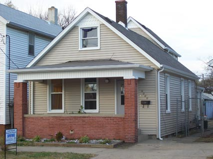 A house with new paint and a brick front porch.