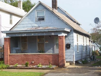 A rundown house with a brick front porch.